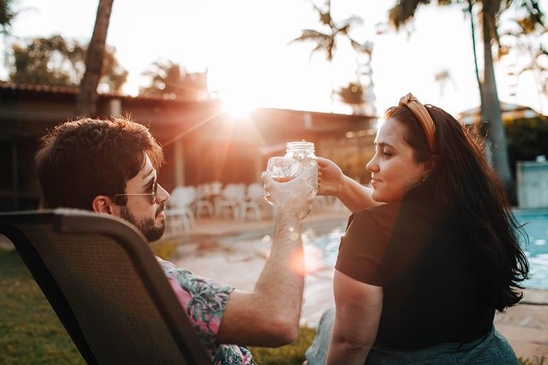 eine selbstbewusste Frau, die einen Toast mit einem Mann hat, während sie in der Nähe des Pools sitzt