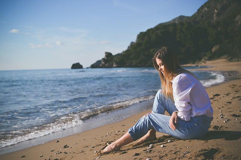 eine traurige Frau, die an der Küste sitzt und in den Sand schaut