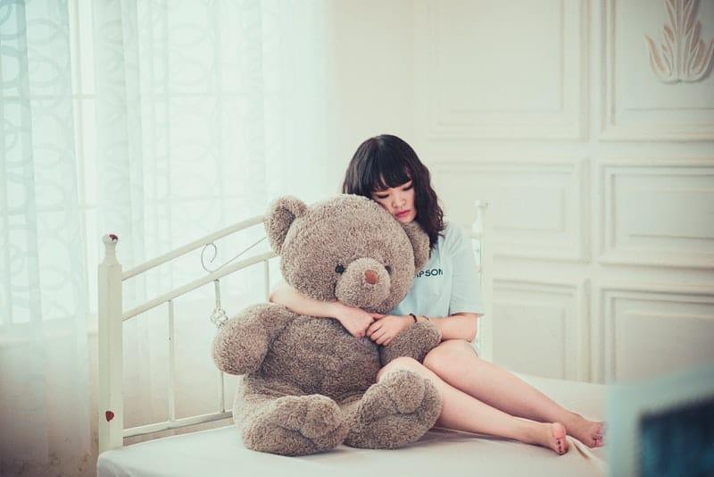 eine traurige Frau, die im Bett sitzt und einen Teddybären umarmt