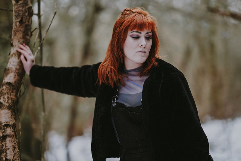 eine traurige Frau, die sich auf das Holz stützt und nach unten schaut