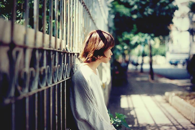 eine traurige Frau, die sich auf den Zaun stützt und nach unten schaut
