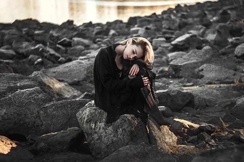 Eine traurige Frau, die sich auf die Knie stützte und alleine auf den schwarzen Felsen saß