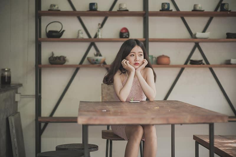 Eine traurige Frau sitzt auf dem Stuhl und lehnt sich auf den Tisch