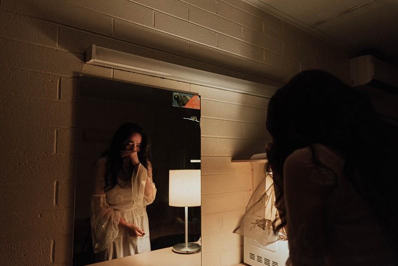 eine weinende Frau vor dem Spiegel, während sie im Raum steht