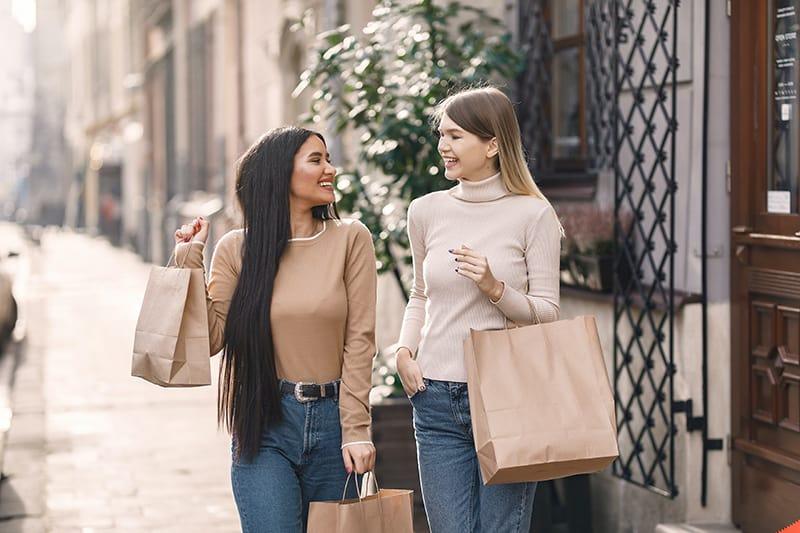 fröhliche Freunde, die Einkaufstaschen tragen und lächeln
