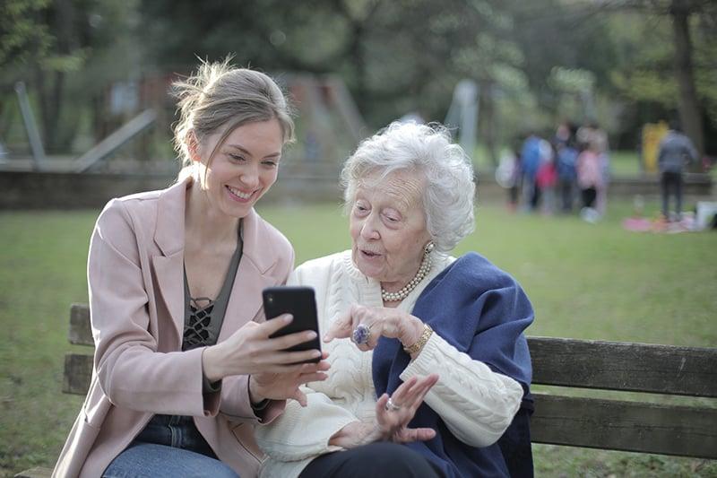 fröhliche Großmutter und erwachsenes Enkelkind, die ein Smartphone während eines Gesprächs beim Sitzen auf der Bank betrachten