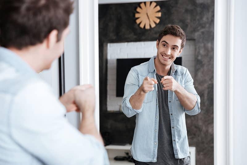 glücklicher Mann, der Spiegel betrachtet