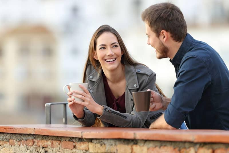 glückliches Paar, das draußen spricht und einen Kaffee trinkt