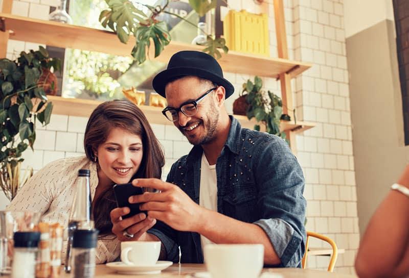 glückliches Paar im Café, das Telefon ansieht
