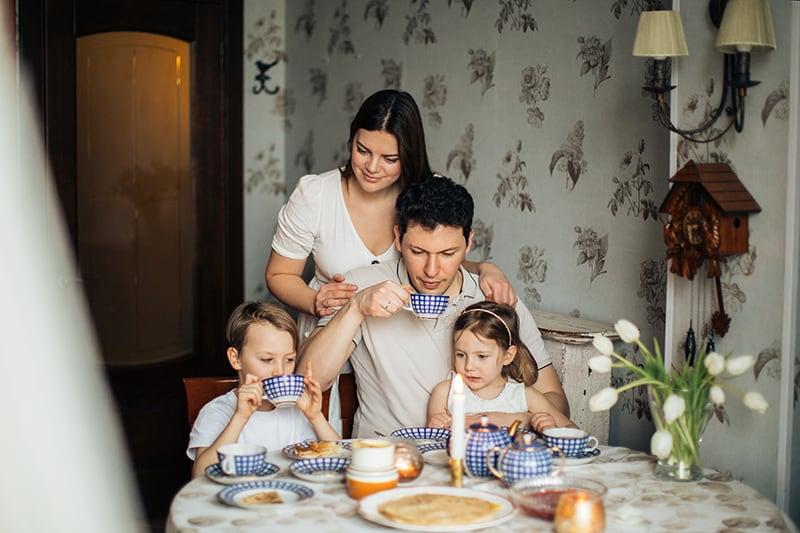 glückliche Familie, die Tee trinkt, während alle einen Vater umgeben