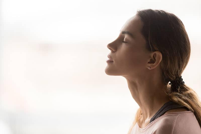 junge Frau atmet tief durch