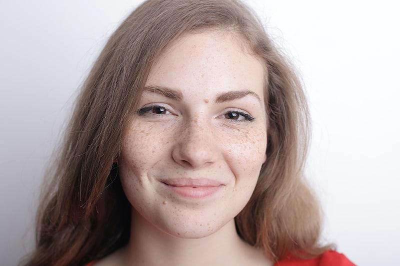 junge Frau mit Sommersprossen im Gesicht ohne Make-up