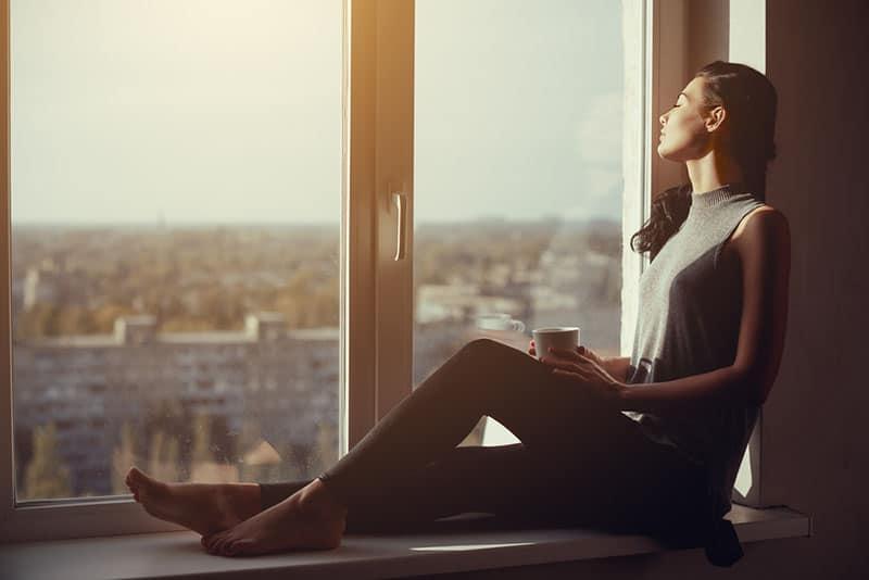 junge Frau sitzt am Fenster