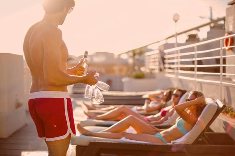 junger Mann bietet sonnenbadende freundinnen am schwimmbad getränke an