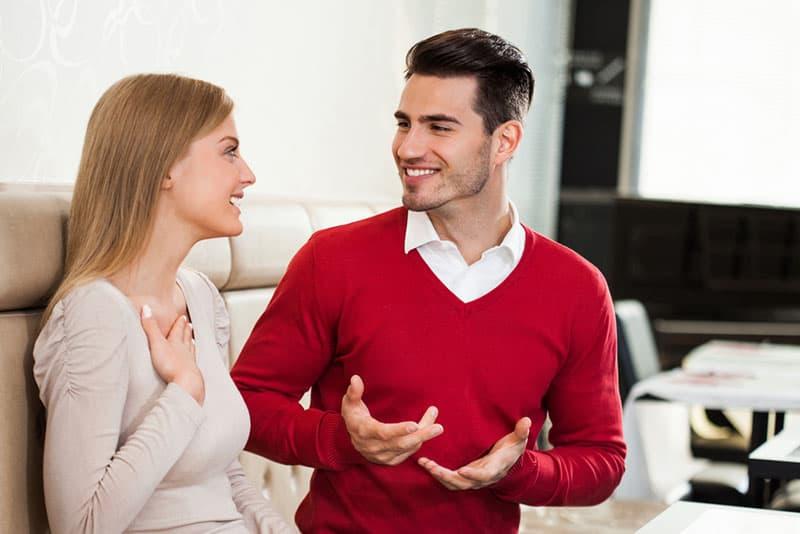 junger Mann spricht mit begeisterter Frau im Café