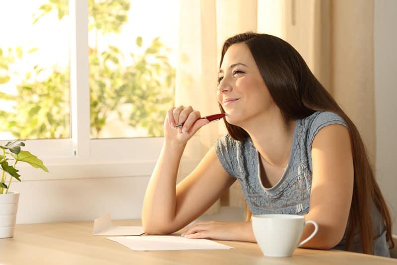 lächelnde Frau, die einen Brief schreibt