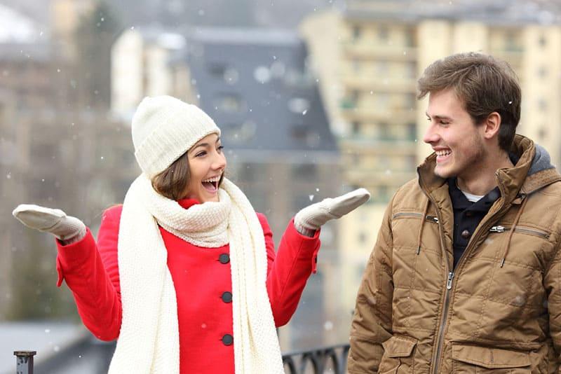 lächelnde Frau, die mit Mann auf dem Schnee steht