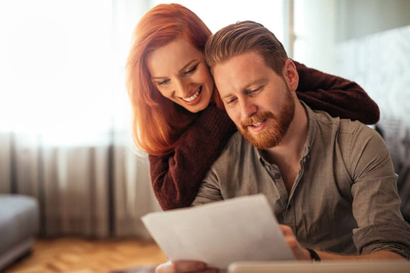 lächelndes Paar, das Papiere betrachtet