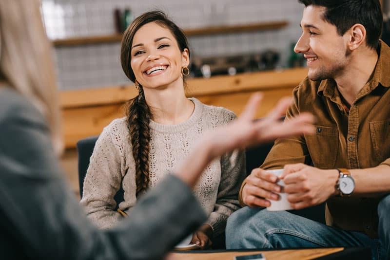 lächelndes Paar im Gespräch mit Freund