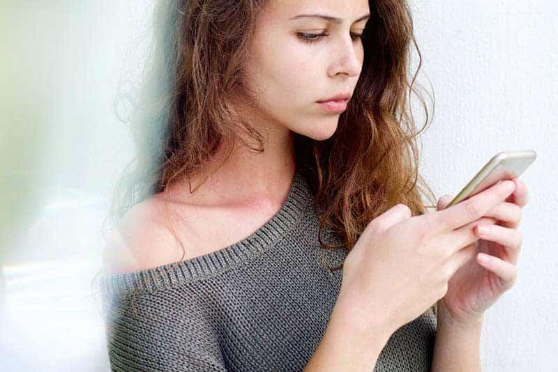 nachdenkliche Frau, die auf ihrem Telefon tippt