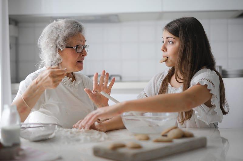 nachdenkliche Großmutter spricht mit Enkelin, während sie am Tisch Kekse macht