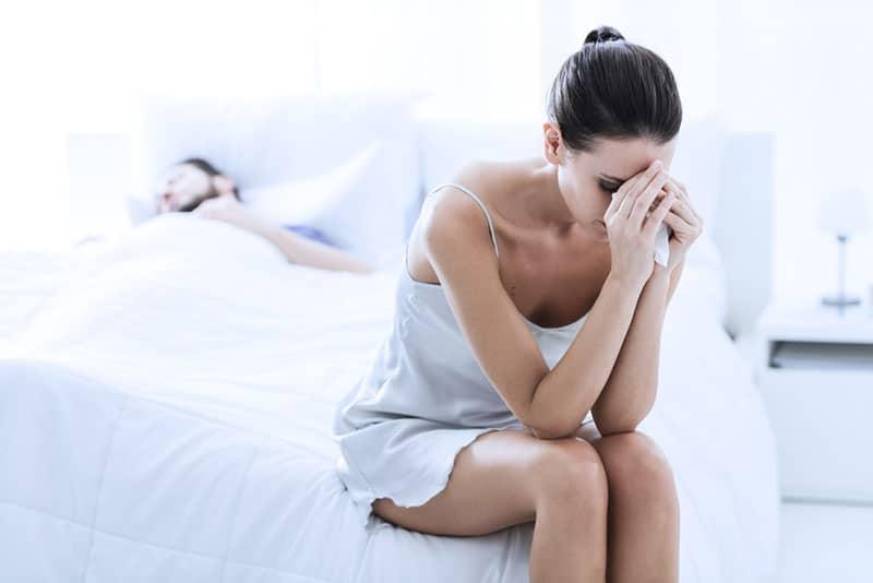 traurige Frau, die auf dem Bett sitzt, während Mann schläft