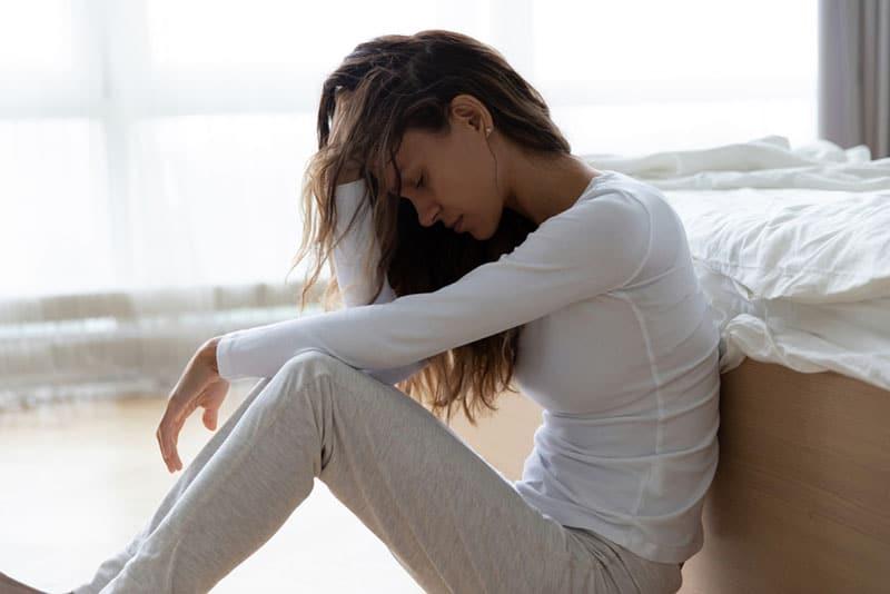 traurige Frau sitzt auf dem Boden