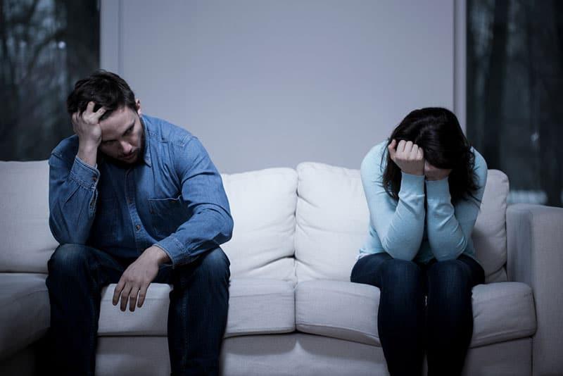 trauriges Paar sitzt auf der Couch auseinander