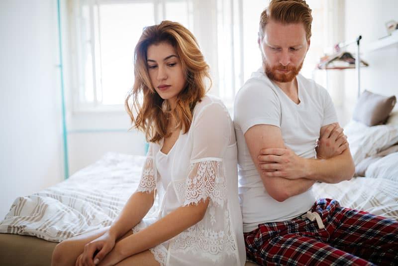 unglückliches Paar sitzt auf dem Bett