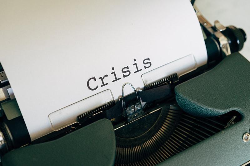 Weißbuch mit dem Wort Krise auf einer Weinlese-Schreibmaschine