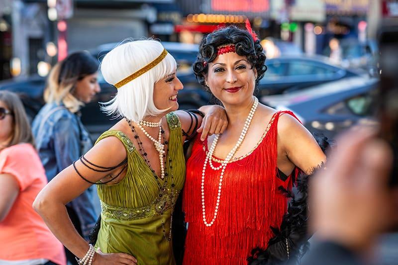 Zwei Frauen mittleren Alters tragen ein Flapper-Kostüm, während sie für die Fotografie posieren