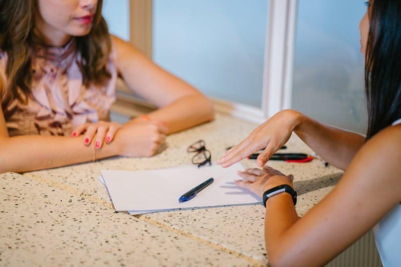 Zwei Frauen unterhalten sich, während sie am Tisch sitzen