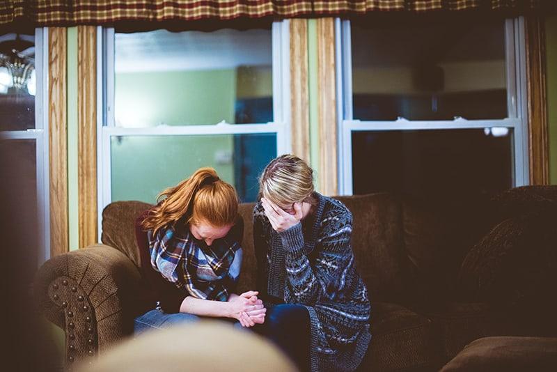 zwei Frauen weinen wegen des Verlustes einer lieben Person, während sie auf dem Sofa sitzen