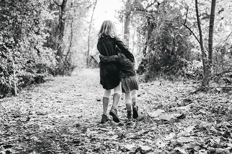 zwei Kinder umarmen sich beim Gehen im Wald