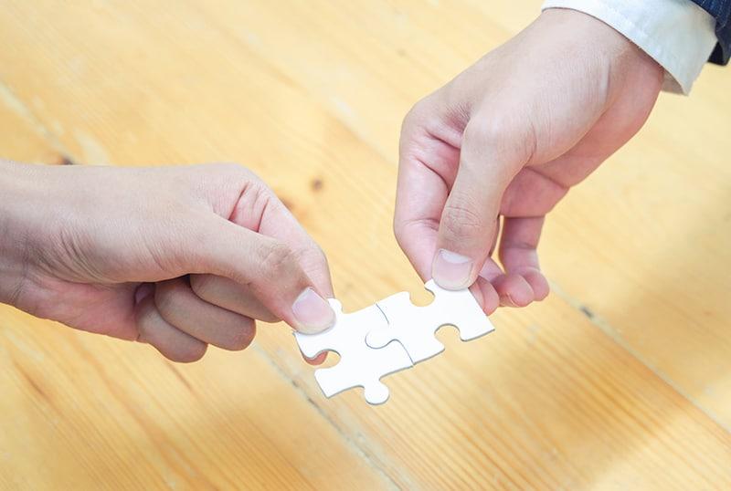 Zwei Personen verbinden zwei Puzzleteile über dem Holztisch