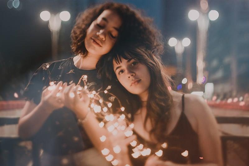zwei Schwestern, die sich aneinander lehnen und Weihnachtslichter in den Händen halten