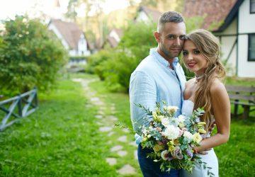 Ein Mann und eine Frau in einer Umarmung mit einem Blumenstrauß stehen in einem Garten