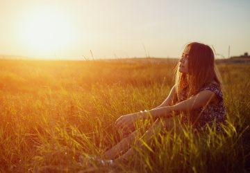 Eine nachdenkliche Frau bei Sonnenuntergang sitzt auf einem Grasfeld