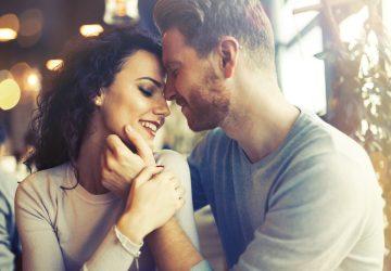ein liebendes Paar, das in einer Umarmung in einem Café sitzt