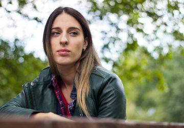 eine Frau, die in einem Park sitzt und traurig nachdenkt