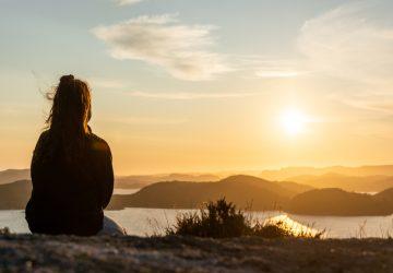 Das Mädchen sitzt auf einem Hügel und beobachtet bei Sonnenuntergang die Landschaft vor sich