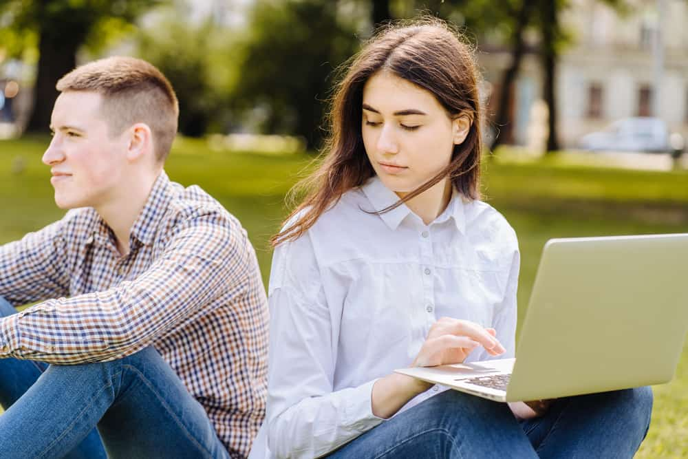 Das Mädchen sieht den Kerl traurig über die Schulter an, als sie im Gras sitzen