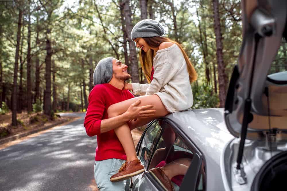 Das Mädchen sitzt auf dem Dach des Autos und kuschelt mit ihrem Freund neben dem Auto