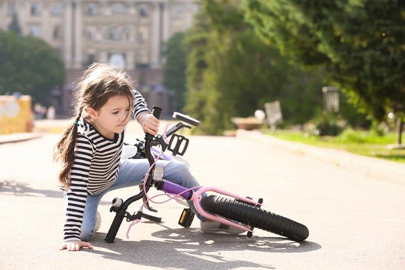 Das süße kleine Mädchen ist unterwegs von ihrem Fahrrad gefallen