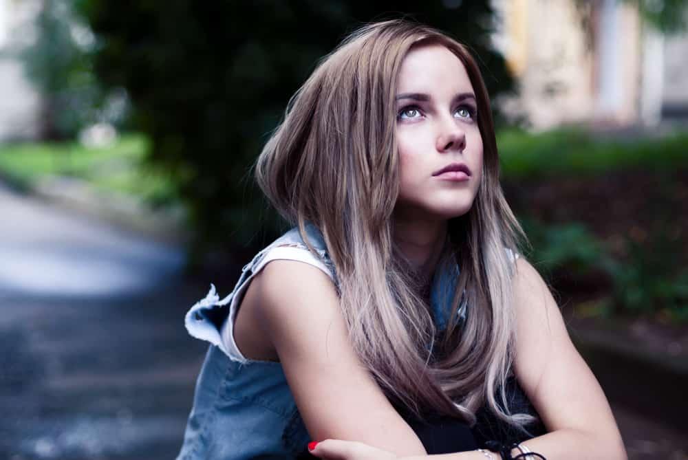 Das verschuldete Mädchen sitzt draußen und schaut in den Himmel