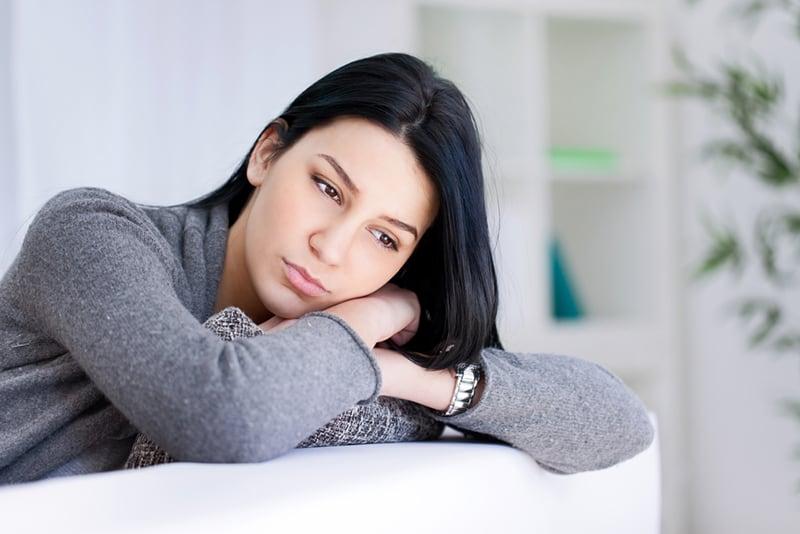 Einsame traurige Frau tief in Gedanken auf der Couch gelehnt
