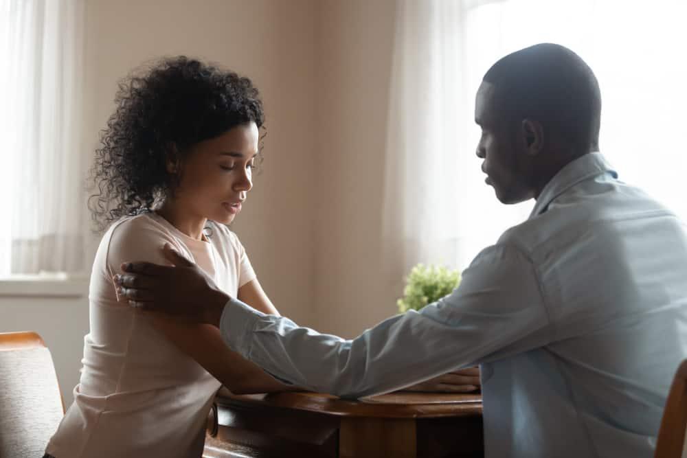 Der Mann tröstet seine verärgerte Frau, als sie am Küchentisch sitzen