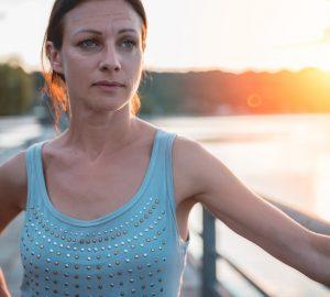 Eine traurige weinende Frau steht bei Sonnenuntergang auf der Brücke