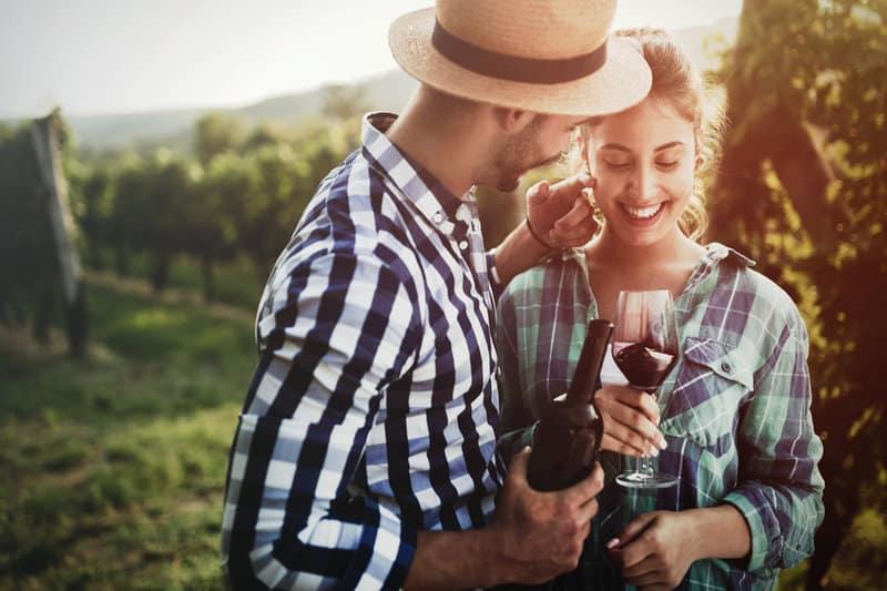Die Frau hält ein Glas in der Hand und lacht, während der Mann eine Flasche hält und die Frau streichelt