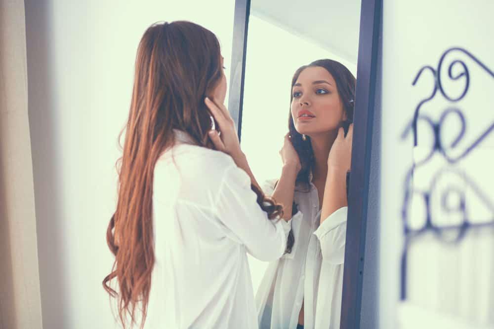 Die Frau schaut in den Spiegel und denkt nach